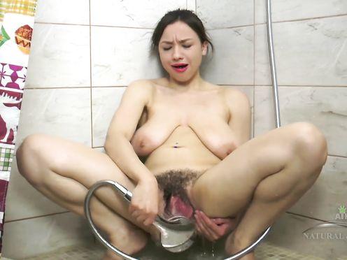 Сисястая шлюха дрочит душем густое волосатое влагалище